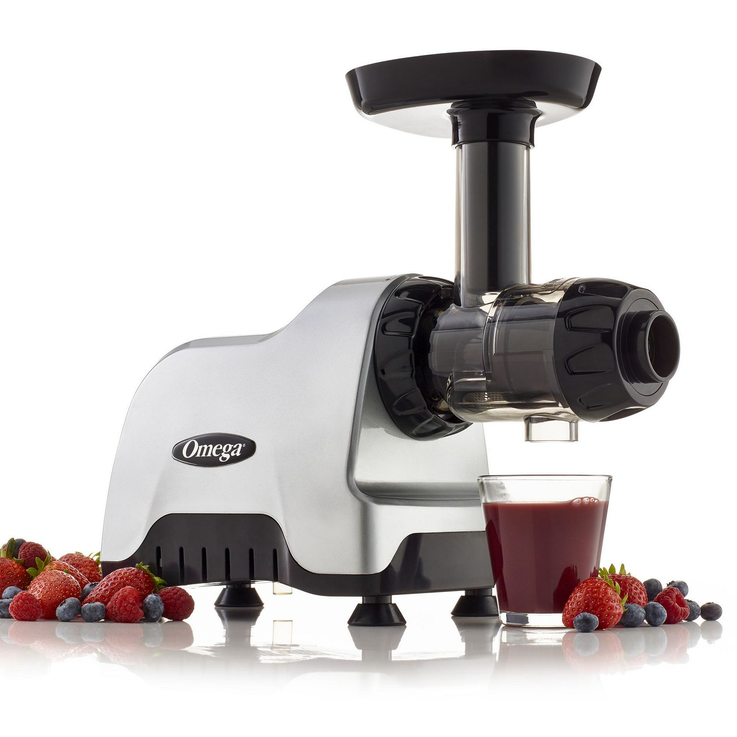 Black and stainless steel Omega compact cold press masticating juicer and nutrition system with sliced berries and glass of juice at its base - best cold press juicer