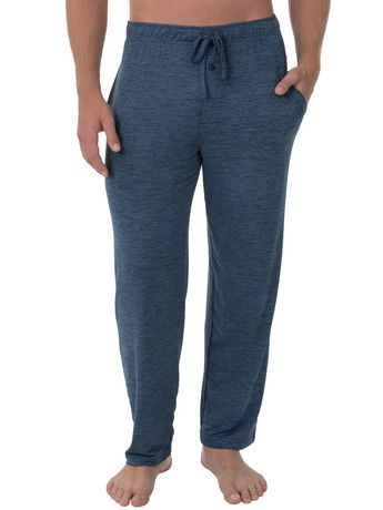 Man from the waist down wearing dark blue pajama pants with drawstring made by Fruit of the Loom