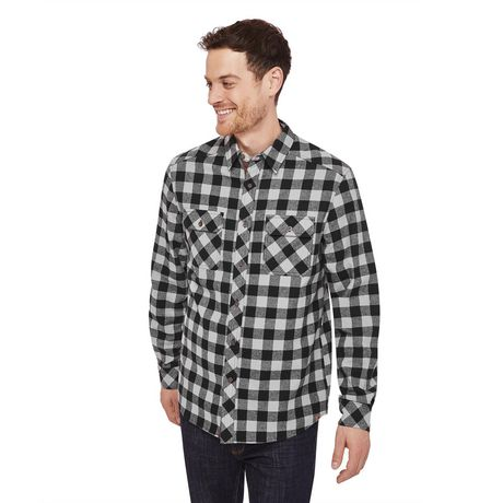 Smiling guy with short dark hair wearing black and grey Canadiana flannel plaid shirt and dark jeans