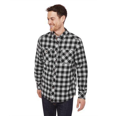 Mec souriant aux cheveux courts et noirs vêtu d'une chemise à carreaux en flanelle Canadiana noire et grise et d'un jean noir