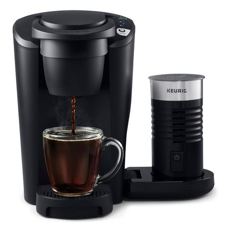 Black single cup coffee maker from Keurig K-Latte with glass mug being filled with coffee