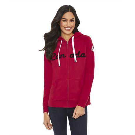 Smiling woman with long brown hair wearing red zip up Canadiana raglan hoodie
