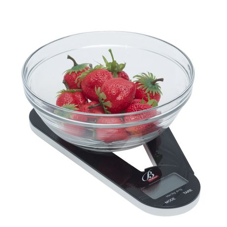 Black folding kitchen scale with glass bowl of strawberries sitting on it