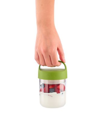 Hand holding a clear plastic jar with green lid with a blueberry and strawberry yogurt mix inside, made by Lékué