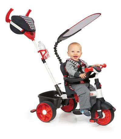 Smiling toddler in grey clothes riding a black and red sports edition trike with grey mesh head cover, made by Little Tikes