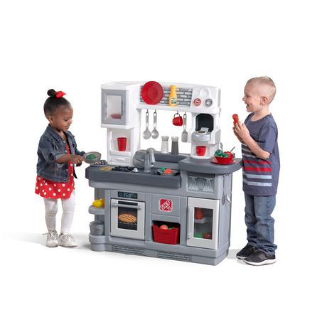 Little boy and girl playing with grey plastic mini kitchen set, made by Little Tikes