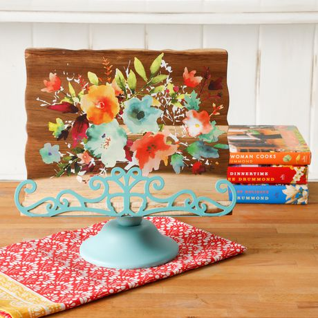 Decorative teal recipe book holder sitting on red and white dish towel on wood countertop with cookbooks in background