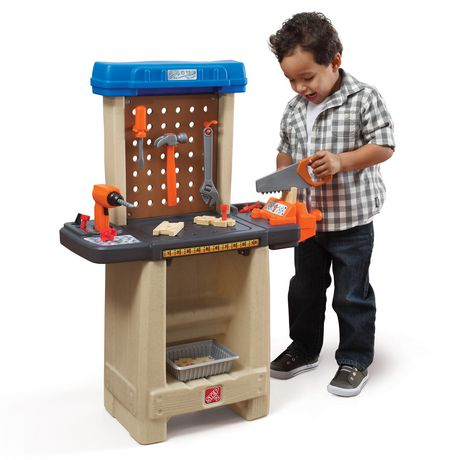 Smiling toddler boy dressed in black-and-white checked shirt and dark blue jeans playing with plastic handyman workbench set, made by Step2