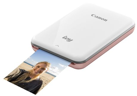 White and rose mini photo printer printing photo of smiling blond woman